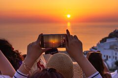 A tourist taking picture of sunset in Santorini, Greece. wish list for 2021.