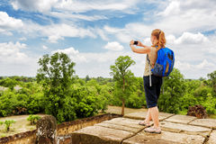 Tourist taking picture from top of temple in Angkor, Cambodia Stock Image