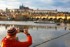 Tourist photographing Prague with Charles Bridge and Hradcany stock image