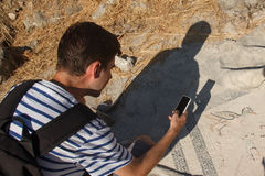 Tourist taking pictures on an old greek mosaic Royalty Free Stock Images