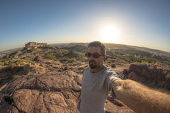 Tourist taking selfie in backlight at Jodhpur fort from above, perched on top dominating the blue town. Travel destination in Raja Royalty Free Stock Photos