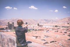 Tourist taking selfie in Cusco, Peru, toned image Stock Photo