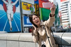 Tourist taking selfie,glico running man. Female tourist taking selfie with an attractive smile in front of the famous glico running man sign stock photography