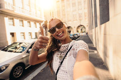 Tourist taking selfie in a street surrounded by buildings. Royalty Free Stock Photo