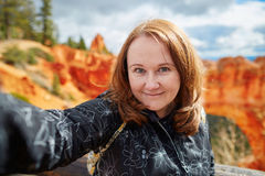 Tourist taking selfie using her mobile phone in Bryce canyon, Utah, USA Stock Photo
