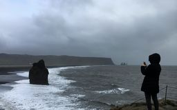 Tourist taking photo of view at Reynsifjara Black Sand Beach. Tourist taking smartphone photo of the view at Reynsifjara Black Sand Beach Stock Images