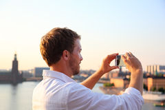 Tourist taking smartphone photograph in Stockholm. Tourist taking photograph of sunset in Stockholm skyline and Gamla Stan. Man photographer taking photos using Royalty Free Stock Photography