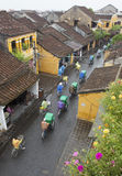 Tourist taking a tour to discover Hoi An ancient town by cyclo on a rainy day Royalty Free Stock Photo