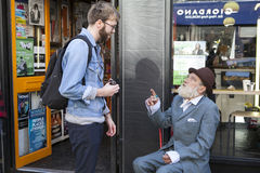 Tourist talking with local homeless on Brick Lane Stock Photo