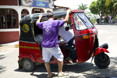 Tourist talks about a journey with the driver of tuk-tuk Stock Image