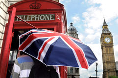 Tourist in telephone box and Big Ben in London. Tourist with British umbrella in telephone box and Big Ben in London Royalty Free Stock Image