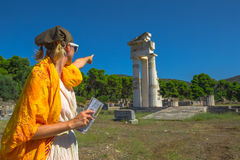 Tourist at Temple of Asklepieion. Tourist woman in Greek dress indicates the ruins of Temple of Asklepieion, Epidaurus, Peloponnese, Greece. The Sanctuary of Royalty Free Stock Photo