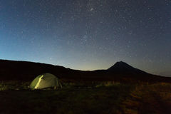 Tourist tent against night sky and Vilyuchinsky stratovolcano. Brookvalley Spokoyny at the foot of outer north-eastern Royalty Free Stock Photos