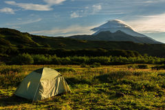 Tourist tent on a background of Vilyuchinsky stratovolcano at dawn. View from brookvalley Spokoyny at the foot of outer Royalty Free Stock Photography