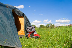 Tourist tent and backpack. Stand on green grass Royalty Free Stock Images