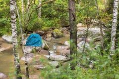 Tourist tent on a boulder in the middle of the Belokurikha mountain river. Belokurikha, Russia - July 30, 2015: Tourist tent on a boulder in the middle of the Stock Photos