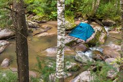 Tourist tent on a boulder in the middle of Belokurikha mountain river. Tourist tent on a boulder in the middle of the Belokurikha mountain river Stock Photography