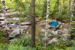 Tourist tent on a boulder in the middle of Belokurikha mountain river. Tourist tent on a boulder in the middle of the Belokurikha mountain river Royalty Free Stock Photo