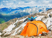 Tourist tent in camp with happy man among mountain landscape Royalty Free Stock Photos