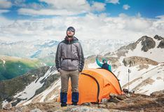 Tourist tent in camp with hiker man among mountain landscape and. Tourist tent in camp with hiker men among mountain landscape and blue sky outdoor Royalty Free Stock Image