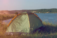 Tourist tent in camp among meadow in the mountains and lake. Stock Image