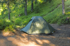 Tourist tent in a clearing in a coniferous forest, illuminated b Royalty Free Stock Photo