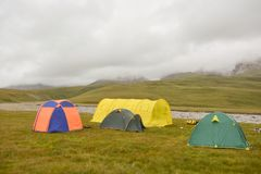 Tourist tent in field camp among montains. Mist, tend, field Stock Photos