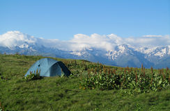Tourist tent on the grass high in the mountains with beautiful rocky peaks covered with snow on the background. The view of rocky peaks with some snow and Stock Images