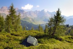 Tourist tent in the green forest on mountains Royalty Free Stock Photo