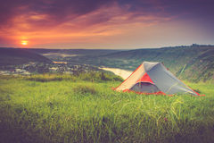 Tourist tent on green meadow at sunset. Camping background. Stock Photos