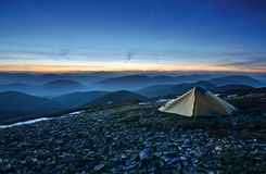 Tourist tent in the rocky mountains and first star Royalty Free Stock Photography