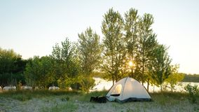 Tourist tent stands on the sandy bank of the river in the summer evening stock photos