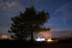 Young couple man and woman having rest at tourist tent and burning campfire on sea shore near forest stock photos