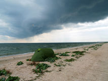 Tourist tent on uninhabited  seashore. Green tent on shelly wild beach under dark-blue sky before heavy thunderstorm Stock Photos