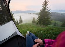 Tourist tent with woman legs in jeans and running shoes. Foggy view of valleys, pine forest and distant mountains with snowy peak from inside of tourist tent stock image