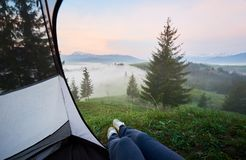 Tourist tent with woman legs in jeans and running shoes. View of foggy valleys, pine forest and distant mountains with snowy peak from inside of tourist tent royalty free stock photography