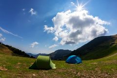 Tourist tents in camp among meadow in the mountain. Summer seaso Royalty Free Stock Photos