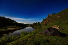 Tourist tents at riverbank at summer night stock photography