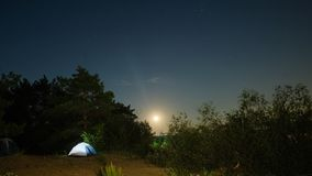 Tourist tents on a sandy beach at night with moonlight surrounded by trees under a starry sky. Advertising background Stock Image