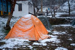 Tourist tents stand in a snow covered camp. In early spring stock photos