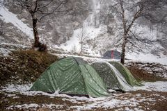 Tourist tents stand in a snow covered camp. In early spring stock photography
