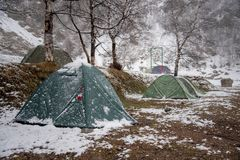Tourist tents stand in a snow covered camp. In early spring royalty free stock image