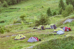 Tourist tents. Tourist tent on a green hillside. Evening camping Stock Images