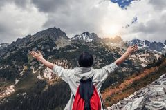 Tourist with hands up stands on the background of a mountain landscape. Tourist with their hands up stands on the background of a mountain landscape Stock Photo