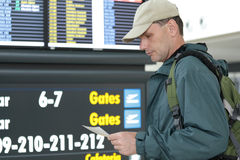 Tourist with tickets. Against the timetable in airport Stock Image