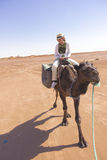 Tourist on top of a camel in the Sahara desert Stock Photo