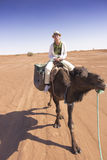 Tourist on top of a camel in the Sahara desert Royalty Free Stock Image