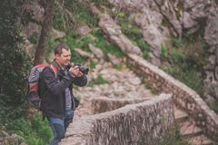 Tourist on a trail checking images on camera stock image
