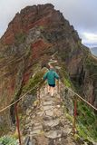 Tourist on the trail on the edge in Madeira. Senior tourist in the mountains of Madeira at Pico do Areeiro Arieiro, while hiking to Pico Ruivo on a cloudy summer stock images