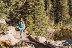 Tourist on trail near Bear Lake in Colorado. Woman tourist walking on trail near Bear Lake at autumn in Rocky Mountain National Park. Colorado, USA Stock Photo